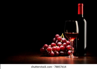 Wine glass and Bottle and red grapes on a wooden table