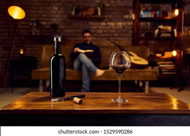Wine glass and a bottle of red wine on table at home man reading book in background. Autumn mood with dark and warm colors.