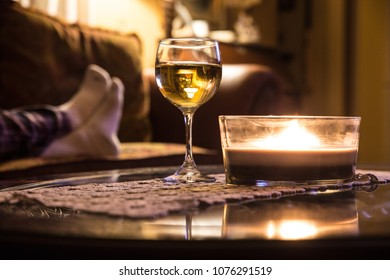 Wine glass and candle in a relaxing scene with persons feet on couch in the background