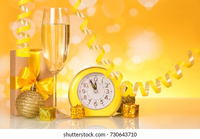 Wine glass with champagne, presents and watches on bright sparkling background