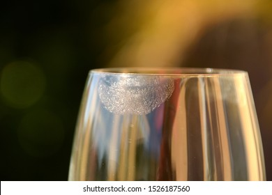 wine glass with clear lipstick macro, close-up of transparent lipstick imprints on wine glass in front of pastel colored background