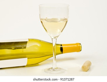 Wine glass with a cork and bottle laying on its side.