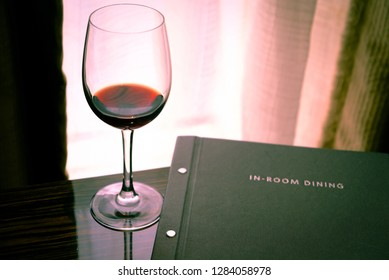 Wine glass and dinner menu on table