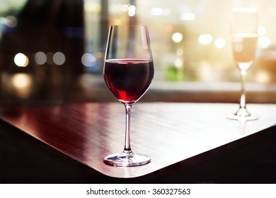 wine glass in entertaining room among sunset window background