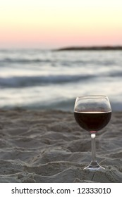 wine glass filled with red wine with the sea in the background