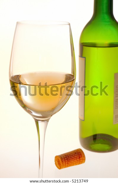 Wine glass filled with white wine, wine bottle and cork on background