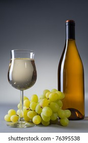 Wine glass filled with white wine in the foreground. Grapes and wine bottle on the gray background.