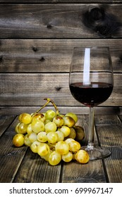 Wine glass and fresh bunch of white grapes photographed on an antique wooden table.