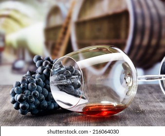 Wine glass with grape on wooden table.