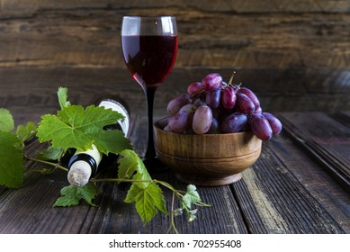 Wine in a glass with grapes on a wooden table close-up