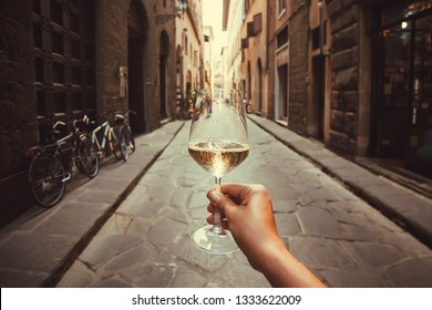 Wine glass in hand of happy tourist walking past historical houses of Florence, Tuscany. Ancient streets in Italy.