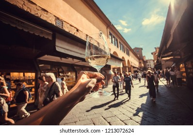 Wine glass in hand of tourist over crowd between old buildings of Florence, Tuscany. Ancient city in Italy. UNESCO World Heritage Site.