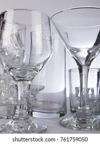 A wine glass and martini glass side by side on a white shelf of other glass.