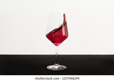 Wine glass on dark table and white background with red wine splashing out of a glass