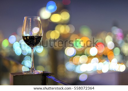 Wine glass with red wine in city bokeh background