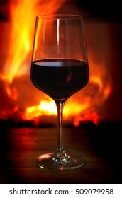 Wine glass with red wine in front of the flames of a burning fireplace on a wooden table.