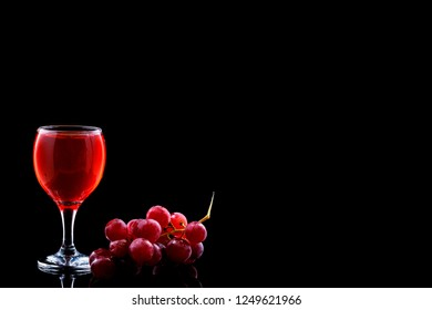 Wine glass and red grapes with drops on blak backgound. Space fot text menu