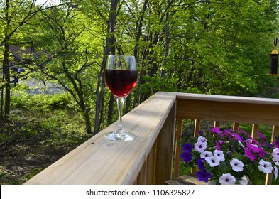 Wine glass with red wine on an outdoor wooden railing with a green nature background a flowers