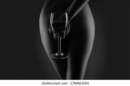 Wine. Glass white wine. Sensual woman holds in hand glass wine. Sensual womans body in dark background. Sensual concept