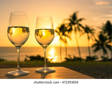 Wine glasses in a beautiful beach resort setting.
