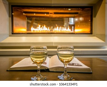 Wine glasses and a book in front of a hotel fireplace