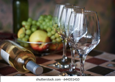 Wine glasses and a bottle of wine on a background of fruit on a serving table