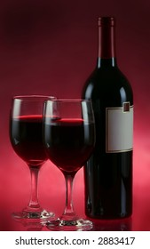 wine glasses and wine bottle on red background