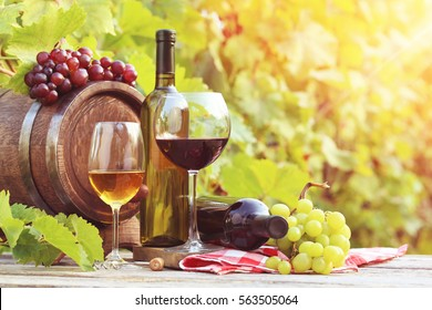 Wine in glasses with bunch of grape on wooden table