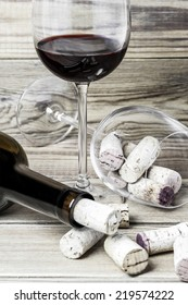 Wine glasses, corks and bottle on a wooden background