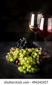 Wine in glasses and different types of grape on dark background. Place for text.