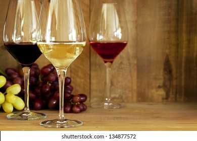 Wine glasses with grapes, against oak background.  Includes red, white, and rose.
