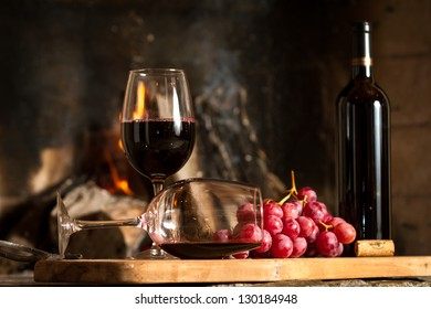 Wine glasses, Grapes, cork and a bottle of wine over a wooden table with fire on the background.