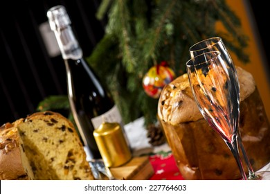 "wine glasses and italian typical christmas cake called ""panettone"" on table wirh christmas tools"