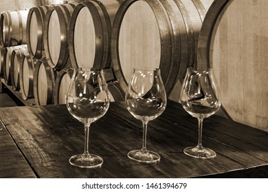 Wine Glasses in a Old, Vintage Wine Cellar with French Oak Barrels Casks of Wine in the background in sepia tone