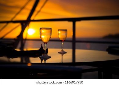 Wine glasses on balcony overlooking at sunset