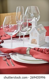 wine glasses on a table with a red tablecloth for the holiday and ceramic candlestick in the form of house