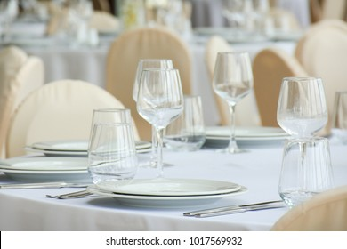 Wine glasses on the white table and white plates with knives and forks.