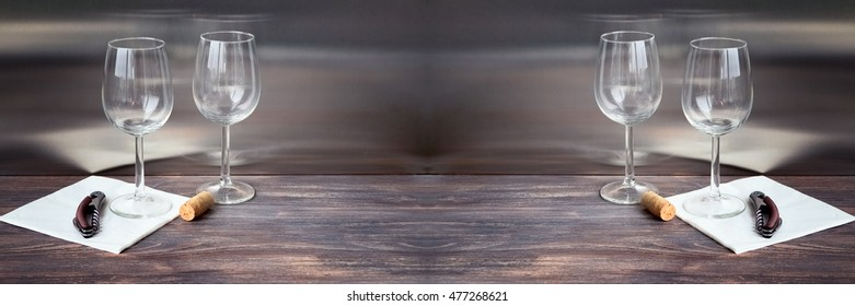 Wine glasses on wooden table. Composition with cork, wine opener, special light. Wide panorama.