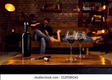 Wine glasses of red wine on table at home couple reading book in background. Autumn or winter mood with dark and warm colors.