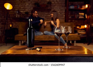 Wine glasses of red wine on table at home happy love couple talking in background.