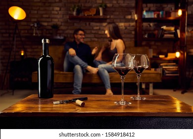 Wine glasses of red wine on table at home happy love couple talking in background. Autumn or winter mood with dark and warm colors.