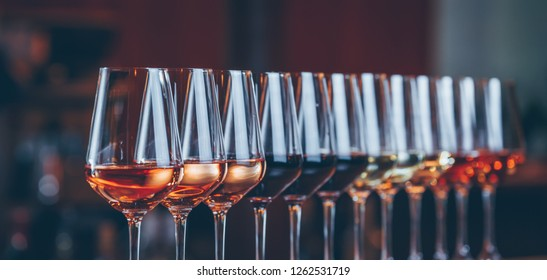 Wine glasses in a row. Buffet table celebration of wine tasting. Nightlife, celebration and entertainment concept. Horizontal, cold toned image, wide screen banner format