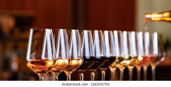 Wine glasses in a row. Pouring wine. Buffet table celebration of wine tasting. Nightlife, celebration and entertainment concept. Horizontal, wide screen banner format