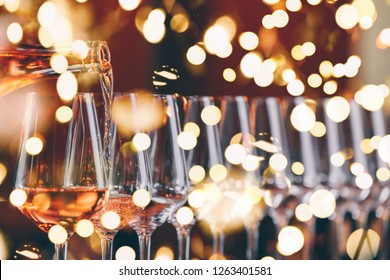 Wine glasses in a row. Pouring wine. Buffet table celebration of wine tasting. Nightlife, celebration and entertainment concept. Horizontal, cold toned image, bright lights bokeh background