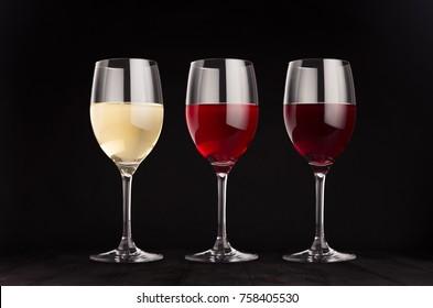 Wine glasses set with red, rose, white wine,  mock up on elegant dark black wooden background.