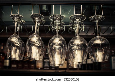 wine glasses in shelf above a bar rack in restaurant