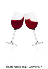 Wine glasses in toasting gesture with splash isolated on white