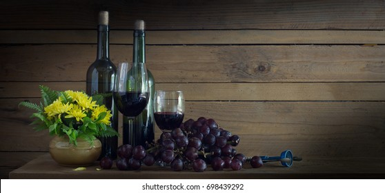 Wine Grape in the bottle and glass with fresh grape and yellow flower in vase all put on the wooden plank. Still Life image and  adjustment size for banner, cover, header