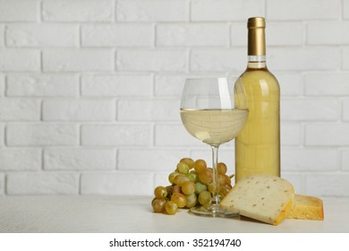 Wine with grape and cheese on brick wall background