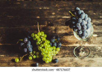 wine grapes in a glass on a wooden table